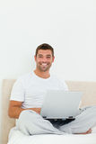 Cheerful man working on his laptop Stock Photography