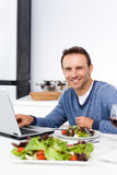 Cheerful man working on his laptop Stock Image