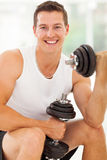 Cheerful man working out. Cheerful young man working out with dumbbells in gym Stock Photo