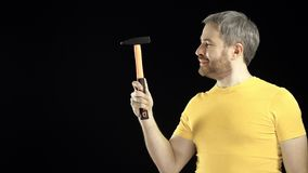 Cheerful man in yellow tshirt holds hammer. DIY, repair, amateur construction or home improvement concepts. Black Royalty Free Stock Photo