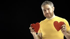 Cheerful man in yellow tshirt holds two red heart shapes. Love, romance, dating, relationship concepts. Black background. Cheerful man in yellow tshirt holds two Royalty Free Stock Photos