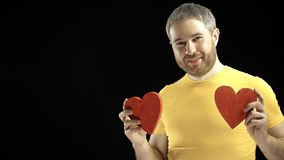 Cheerful man in yellow tshirt holds two red heart shapes. Love, romance, dating, relationship concepts. Black background stock footage