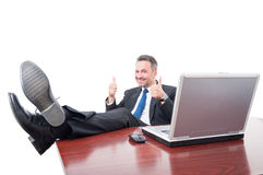 Cheerful manager with feet on desk Stock Photo