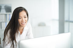 Cheerful manager. Cheerful young manager looking at computer screen Stock Images