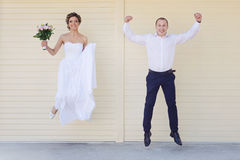 Cheerful married couple jumping Stock Images