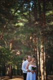 Cheerful married couple kiss in the forest Royalty Free Stock Images