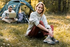 Cheerful married couple relaxing in forest. Full length portrait of joyful young women sitting on grass with relaxation. She is looking at camera and smiling Stock Photo