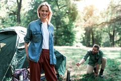 Cheerful married couple resting in the nature. Happy family moments. Portrait of joyful young women standing in forest and smiling. He husband is pitching a tent Royalty Free Stock Image