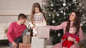 Happy friendly family is folding gifts under big Christmas tree. Cheerful married couple with their two little children is sitting on a floor near new year stock video