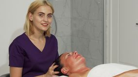 Young professional female therapist smiling to the camera while working. Cheerful masseuse smiling to the camera while giving her female client head massage royalty free stock photography