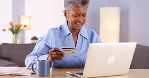 Cheerful Mature African woman buying things online Royalty Free Stock Images