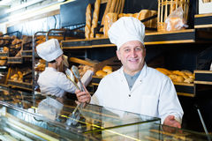Cheerful mature bakers with fresh bread in bakery Stock Photography