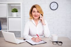 Cheerful mature business woman sitting in office, talking by phone and writing something on clipboard stock photography