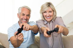 Cheerful mature couple playing video game on sofa Stock Images