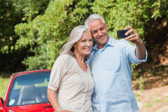 Cheerful mature couple taking pictures of themselves Stock Photography