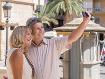 Cheerful mature couple taking selfie pictures of themselves in holidays. Happy mature senior couple of tourists posing for a on their mobile phone as a memento Royalty Free Stock Photos
