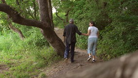 Cheerful Mature couple walking in the forest. Cheerful middle-aged couple walking in forest Park, man funny jumps to the side stock video footage