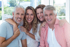 Cheerful mature couples in restaurant. Cheerful mature couples with arms around in restaurant Stock Photos