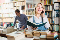 Cheerful mature female chatting on mobile phone. In book store Royalty Free Stock Image