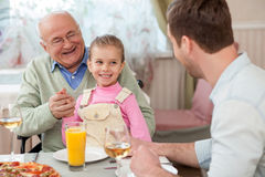 Cheerful mature grandfather is dining with his children. Cute family has dinner in restaurant. They are talking and laughing. The old men is sitting on Royalty Free Stock Image