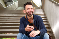 Cheerful mature guy with mobile phone. Portrait of cheerful mature guy with mobile phone sitting outdoors on stairs and laughing stock photo