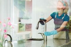 Housewife scrubbing steel sink faucet Stock Photos