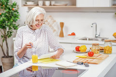 Cheerful mature housewife settling household chores Royalty Free Stock Photos