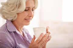Cheerful mature lady drinking hot beverage Stock Photo