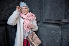 Cheerful mature lady posing near concrete wall of historic building Stock Photos