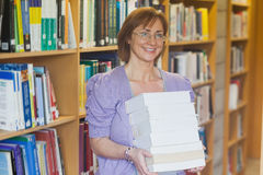 Cheerful mature librarian posing holding a stack of books Royalty Free Stock Photo