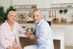 Cheerful mature loving couple family sitting at the kitchen stock photo