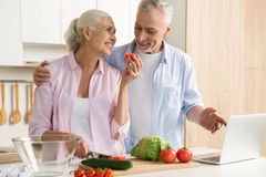 Cheerful mature loving couple family using laptop and cooking Royalty Free Stock Photo