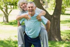 Cheerful mature man carrying woman at park Royalty Free Stock Images