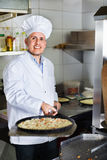 Cheerful mature man cook making pizza in pan on kitchen Stock Photography