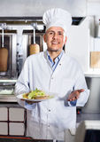 Cheerful mature man cook serving fresh kebab dish on plate Royalty Free Stock Image