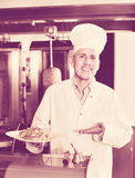 Cheerful mature man cook serving fresh kebab dish on plate Stock Photos