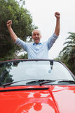 Cheerful mature man enjoying his red convertible Royalty Free Stock Images