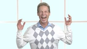 Cheerful mature man laughing indoors. stock footage