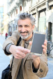 Cheerful mature man showing smartphone Stock Images