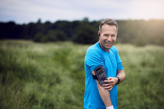 Cheerful mature man with smartphone on his arm. Listening to music while standing in meadow royalty free stock photo