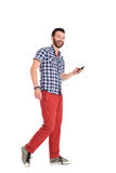 Cheerful mature man walking with cell phone. Full body portrait of cheerful mature man walking with cell phone over white background royalty free stock images