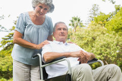 Cheerful mature man in wheelchair with his partner Stock Photography