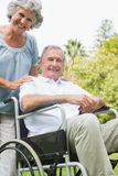Cheerful mature man in wheelchair with partner Royalty Free Stock Image