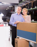 Cheerful mature married couple in shop packed household applianc Stock Photography