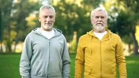 Cheerful mature men in sportswear smiling, posing for camera, healthy lifestyle. Stock photo royalty free stock image
