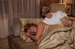 Excited married couple laughing in bed royalty free stock images