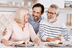 Cheerful mature son hugging elderly parents at home. Thanking my parents for everything . Smiling careful handsome men having dinner and enjoying time with his Royalty Free Stock Image