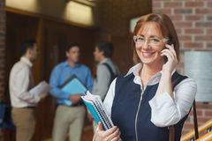 Cheerful mature student phoning with her smartphone Stock Photos