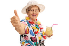 Cheerful mature tourist holding cocktail and a thumb up Stock Photos