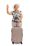 Cheerful mature tourist with a suitcase waving Royalty Free Stock Photos